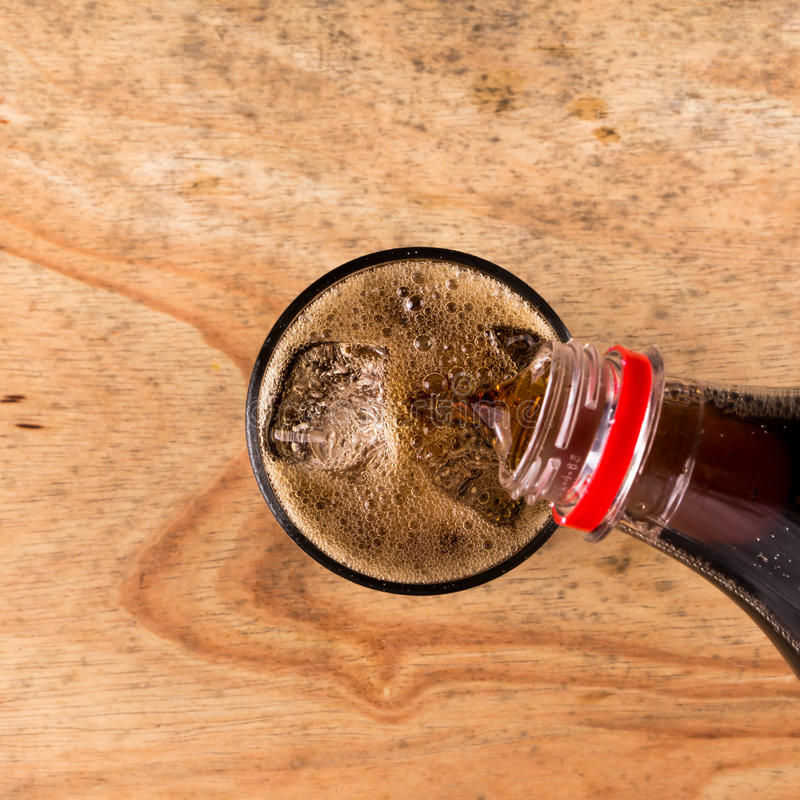 Pouring cola into the glass on wooden table royalty free stock photos