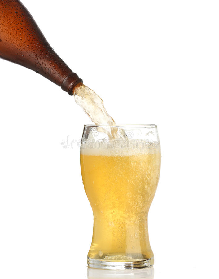 Pouring cold beer into glass. Isolated on white royalty free stock photo