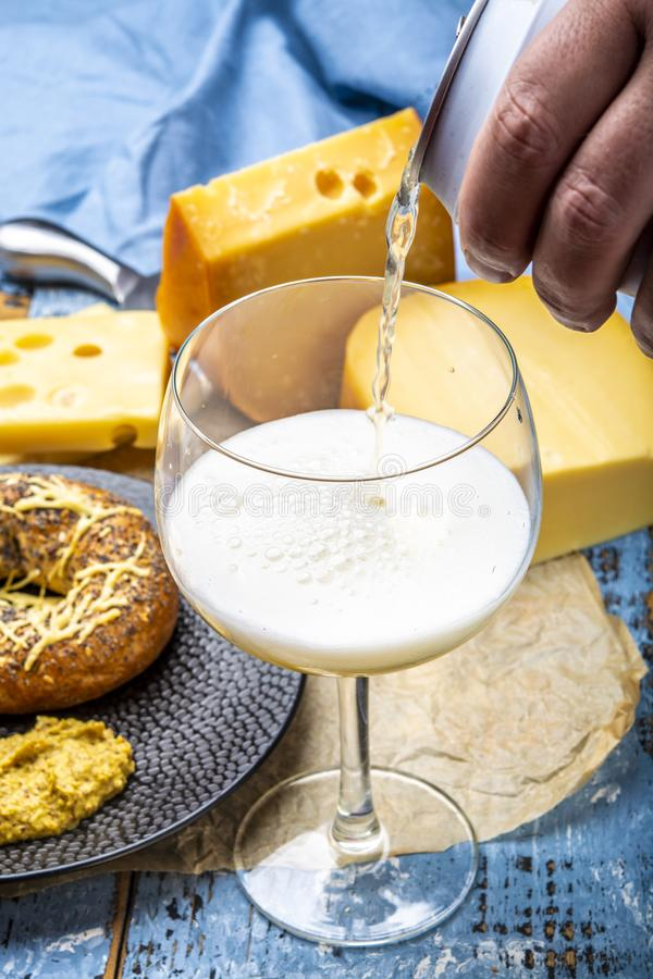 Pouring of cold belgian beer in glass, served in cafe with variety of hard cheeses, tasty european food royalty free stock image