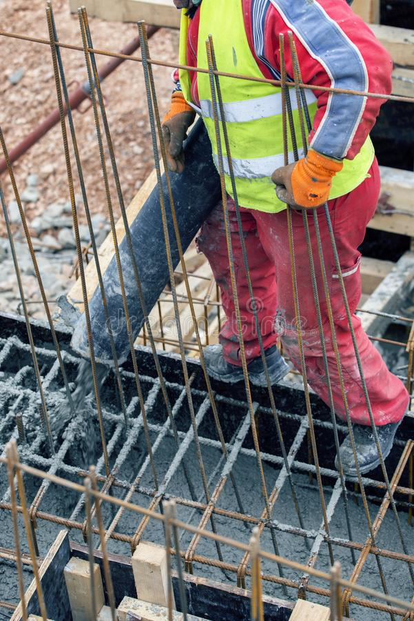 Pouring concrete from cement mixer on concreting formwork. Pour concrete footings foundation with pumptruck royalty free stock photography