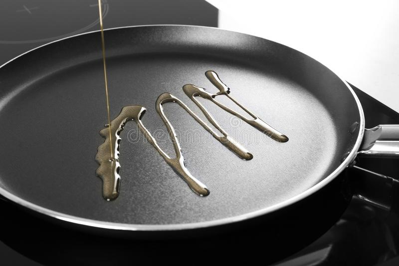 Pouring cooking oil into frying pan,. Closeup royalty free stock photos