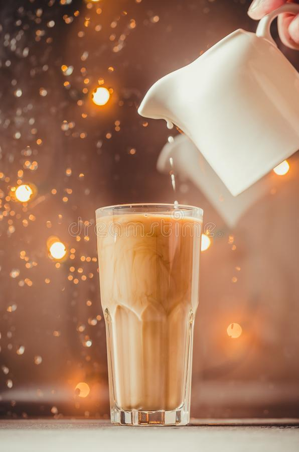 Pouring cream from white creamer into hot coffee in a glass stock images