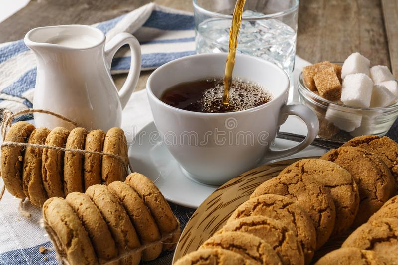 Pouring into the cup tea, sugar and cookies. Sweet breakfast: tea, pouring into the cup, milk in a little jug, sweet biscuits, sugar, and a glass of ice water stock images