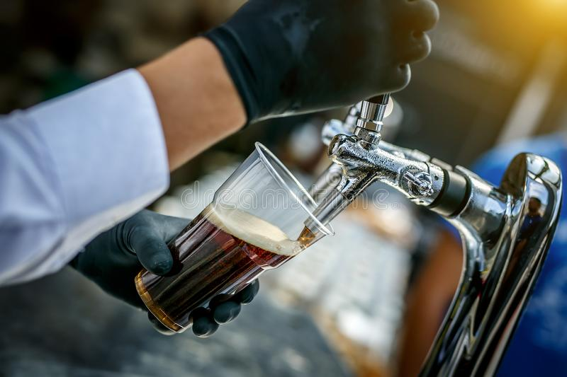 Pouring dark beer to plastic glass from beer tap. royalty free stock images