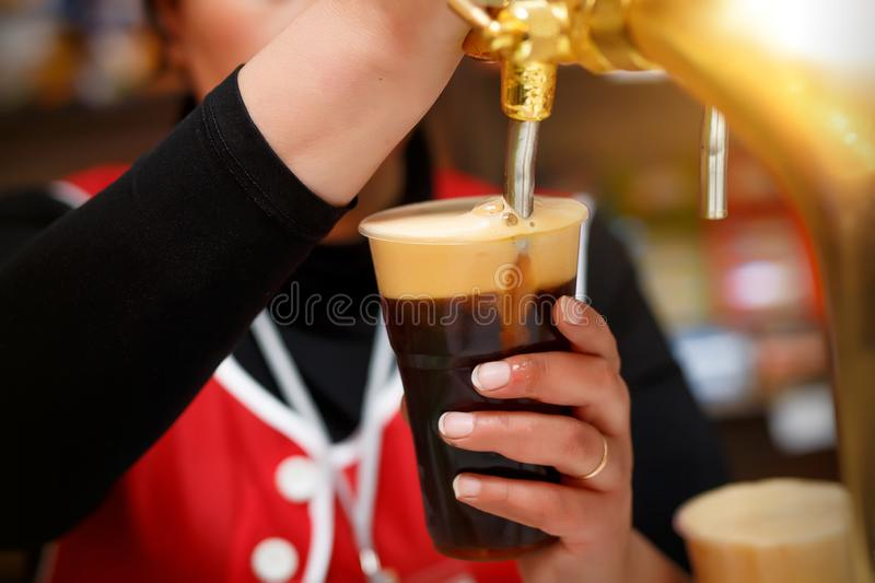 Pouring dark beer to plastic glass from beer tap. stock images