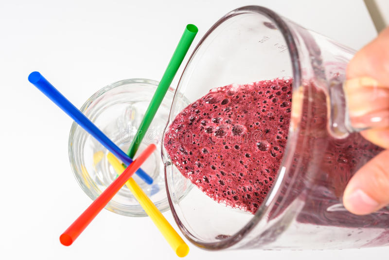 Pouring delicious raw smoothie into a glass royalty free stock photo