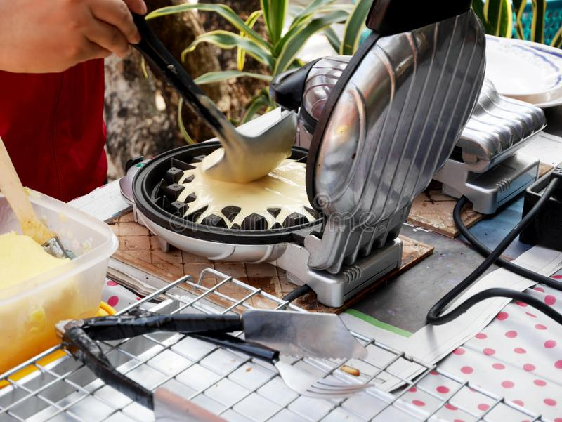Pouring dough on waffle maker royalty free stock image
