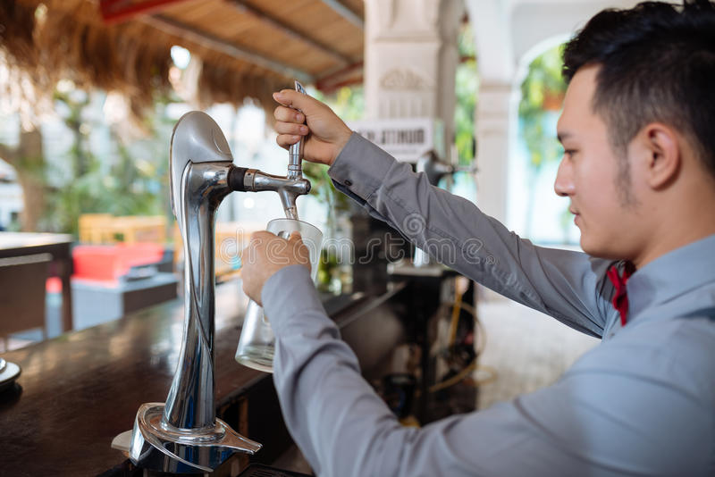 Pouring draft beer. Bartender pouring fresh draft beer from a tap royalty free stock photo