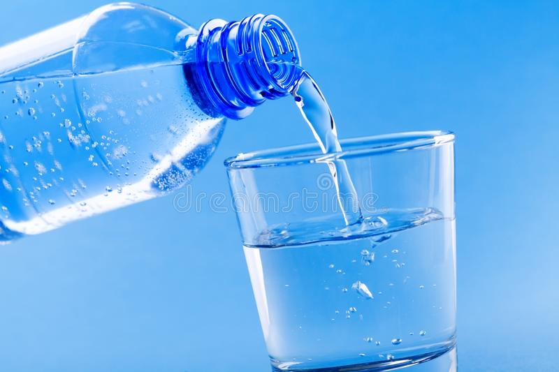 Pouring drinking water from bottle into glass on blue background. Pouring fresh drinking water from bottle into glass on blue background royalty free stock photography