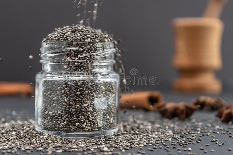 Pouring dry chia seeds in glass jar with unfocused objects on background. Copy space. Paleo diet, chia superfood concept stock image