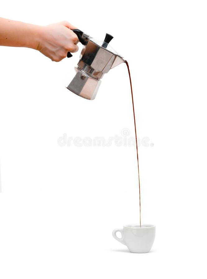 Pouring espresso from silver moka pot to porcelain cup. stock photo