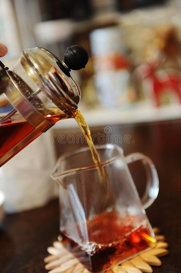 Pouring fresh brewed black tea from a french press into a glass serving jug stock photos