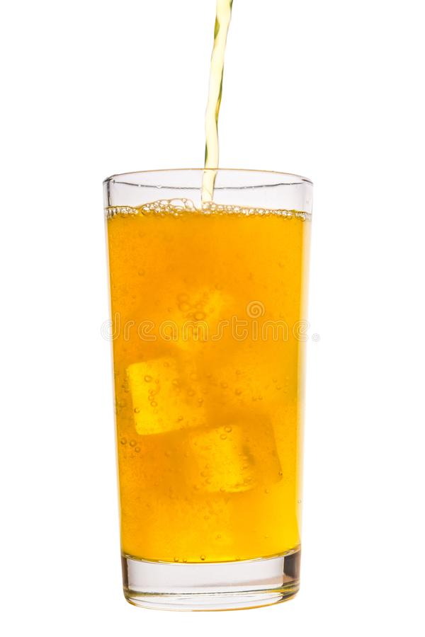 Pouring drink yellow soda with ice cubes in glass isolated on white background, concept of refreshing summer drink. Pouring fresh drink yellow soda with ice royalty free stock photo