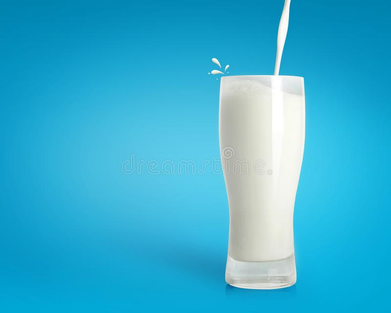 Pouring fresh milk in glass on blue background. Healthy drink background. Milk galss royalty free stock images