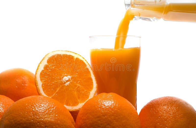 Pouring fresh orange juice. On a white background stock photos