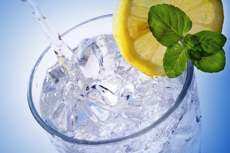Pouring fresh water into a glass with ice cubes, lemon slice and royalty free stock photos