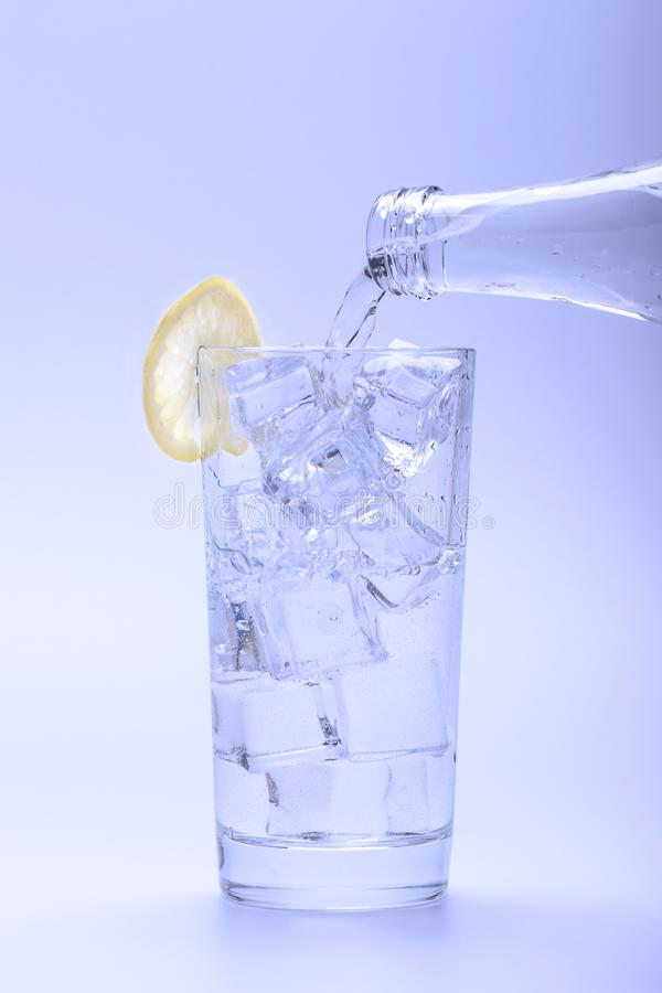 Pouring fresh water into glass with ice and lemon from bottle stock images