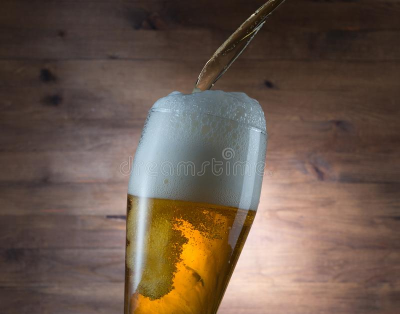 Pouring glass of beer. On wooden background royalty free stock photos