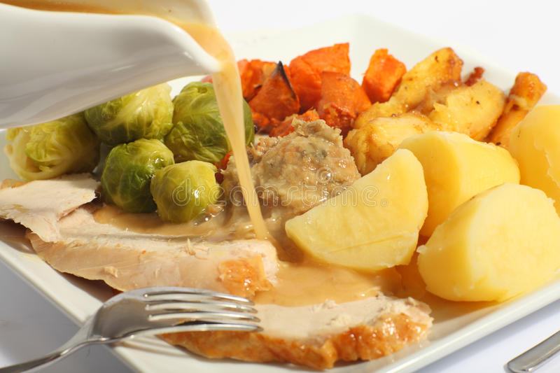 Pouring gravy on a roast turkey meal stock photos