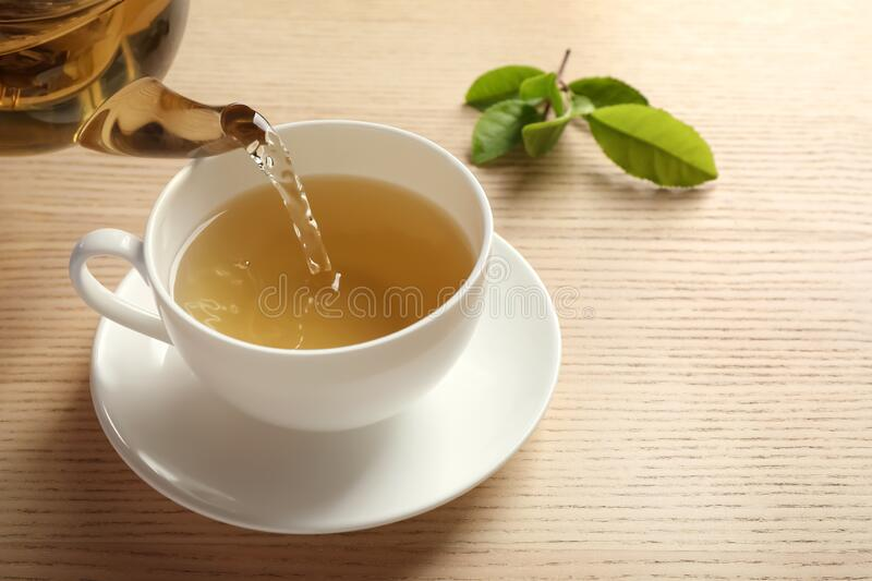 Pouring green tea into cup on wooden table. Space for text. Pouring green tea into cup on wooden table royalty free stock image