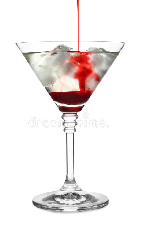 Pouring grenadine into glass of martini cocktail. On white background royalty free stock photo