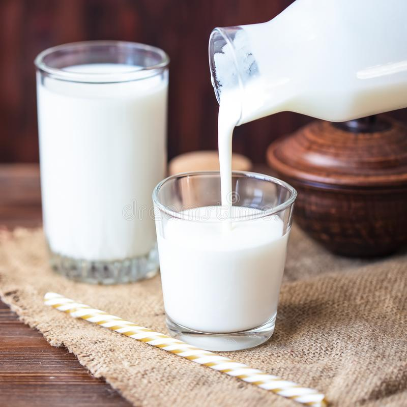 Pouring homemade kefir, yogurt with probiotics Probiotic cold fermented dairy drink Trendy food and drink Copy space Rustic style.  stock photography