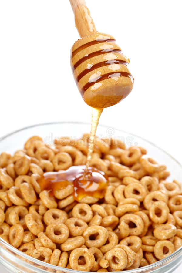 Pouring honey on cornflakes royalty free stock photography