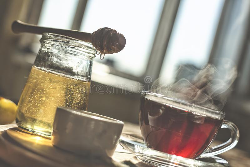 Natural bee honey with morning tea. Pouring honey. stock images