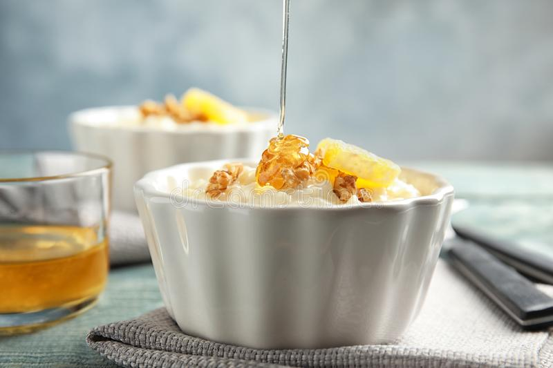 Pouring honey onto rice pudding with walnuts and orange slice in ramekin stock photography