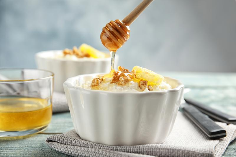 Pouring honey onto rice pudding with walnuts and orange slice in ramekin. On table stock image