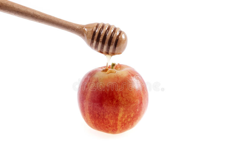 Pouring honey on red apple with a honey dripper. Isolated on white background stock photography