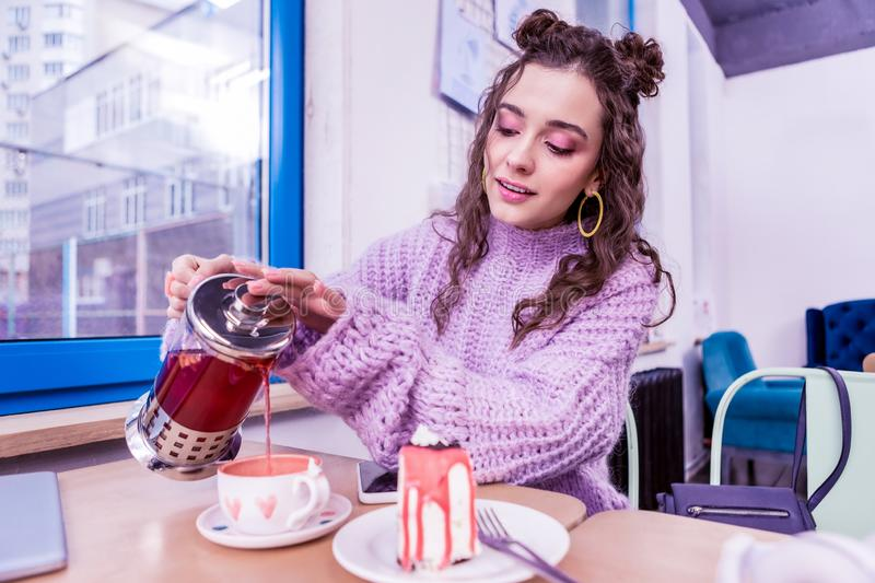Concentrated dark-haired girl adding more tea into cup. Pouring hot tea . Concentrated dark-haired girl adding more tea into cup decorated with watercolor hearts royalty free stock photos