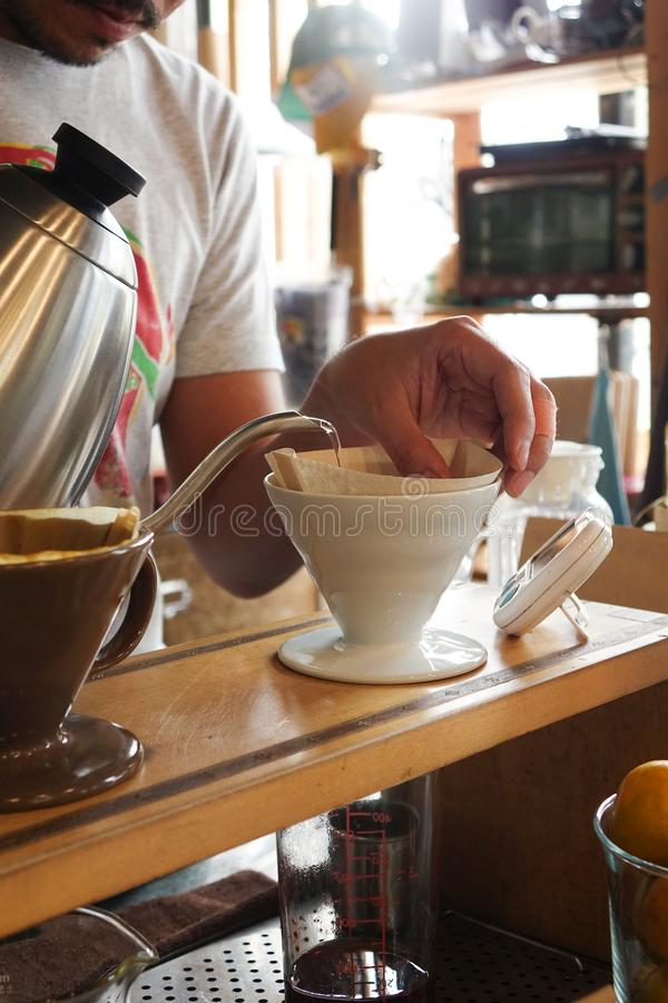 Pouring hot water into coffee drip filter stock photo