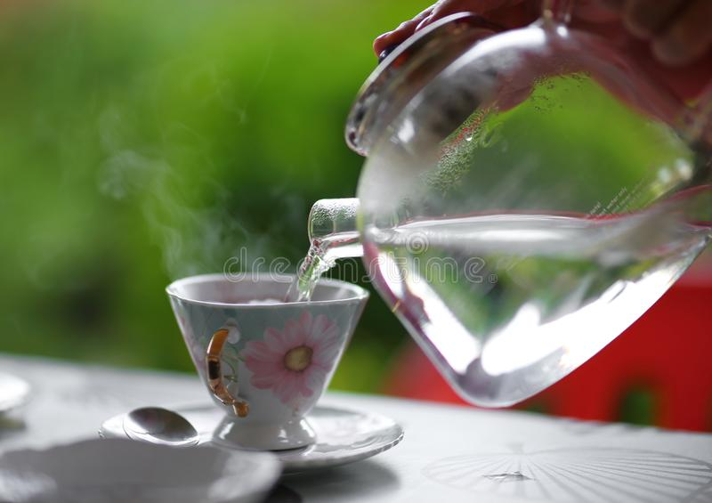 Pouring hot water from glass teapot into the tea cup, summer outdoor. royalty free stock photography