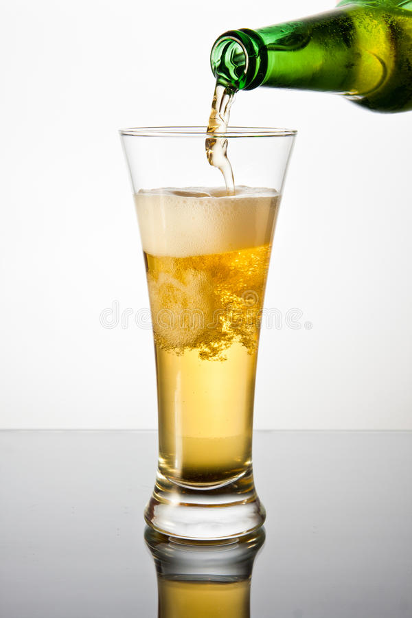 Beer. Pouring lager beer into high glass from green bottle royalty free stock photography
