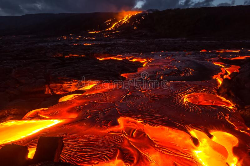 Pouring lava on the slope of the volcano. Volcanic eruption and magma. stock photography