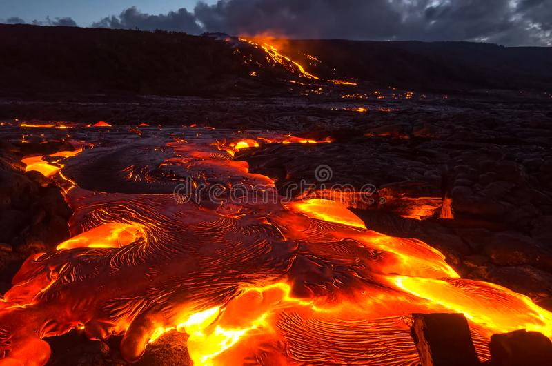 Pouring lava on the slope of the volcano. Volcanic eruption and magma. Pouring lava on the slope of the volcano. Volcanic eruption and magma stock photo