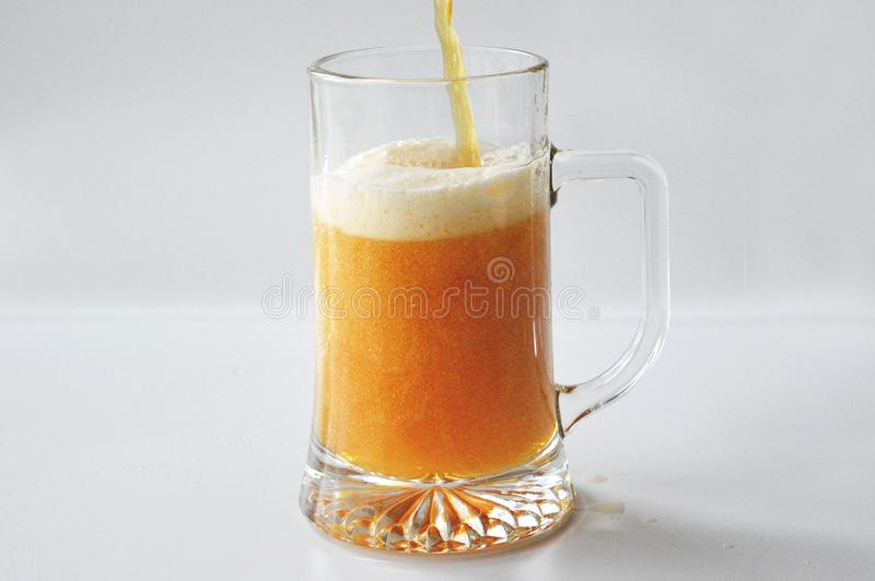 Pouring beer into a glass. Pouring light beer into a glass. Beer in a bottle. A half-liter glass on a white background royalty free stock photos