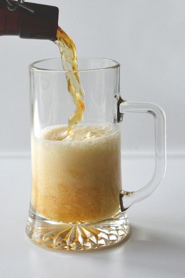 Pouring beer into a glass. Pouring light beer into a glass. Beer in a bottle. A half-liter glass on a white background stock photo