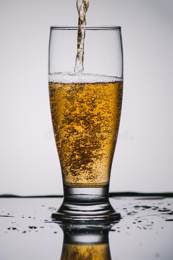 Pouring light beer into transparent glass stock image