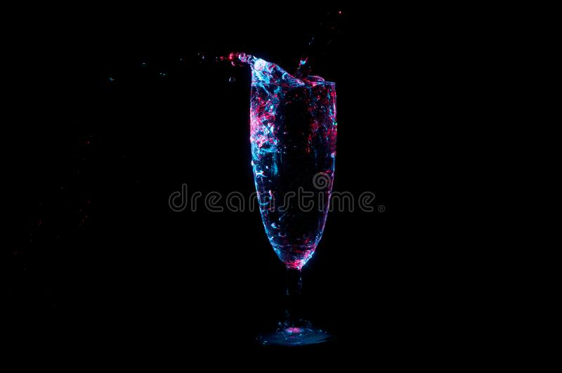 Pouring liquid into champagne flute in blue and red light on a black background royalty free stock image