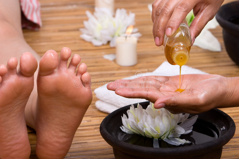 Pouring massage oil. The beautician is pouring the aromatic massage oil into her hand royalty free stock photos