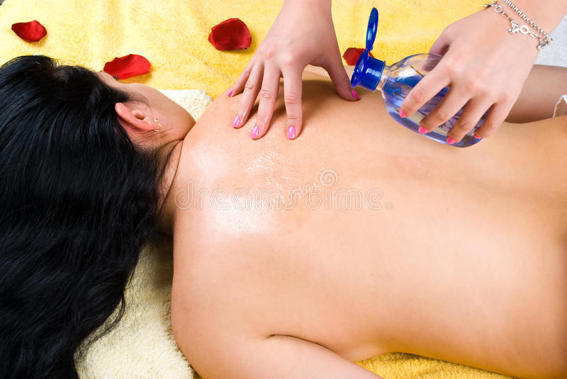 Pouring massage oil on woman back at spa royalty free stock photography