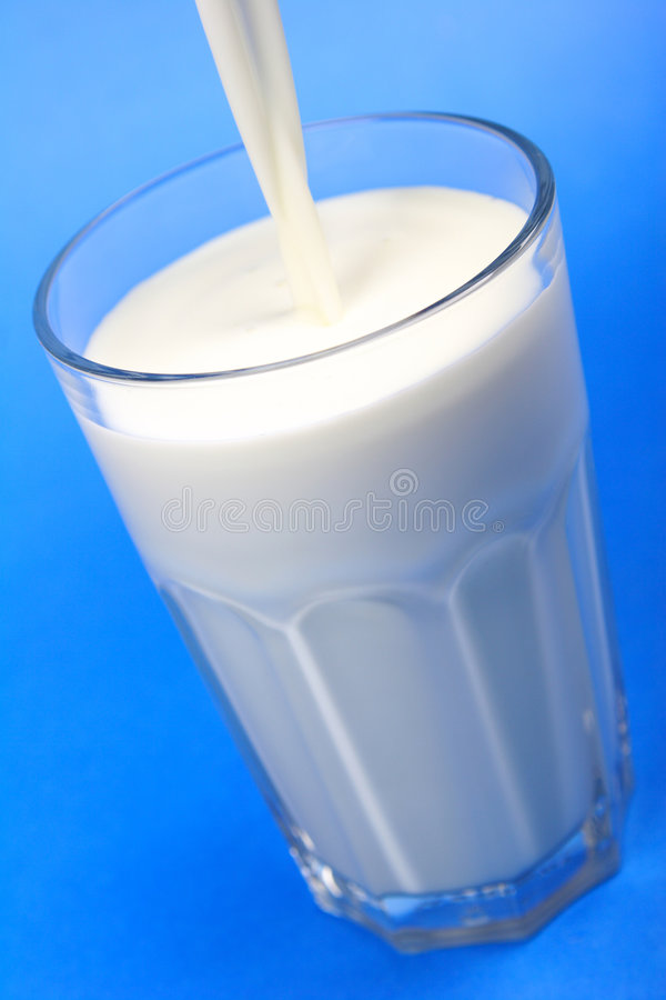 Pouring of milk. Pouring for glass of milk on blue background stock photos