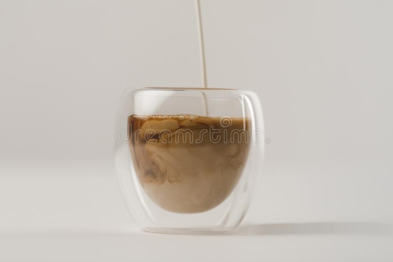 Pouring milk in cup with coffee stock photo