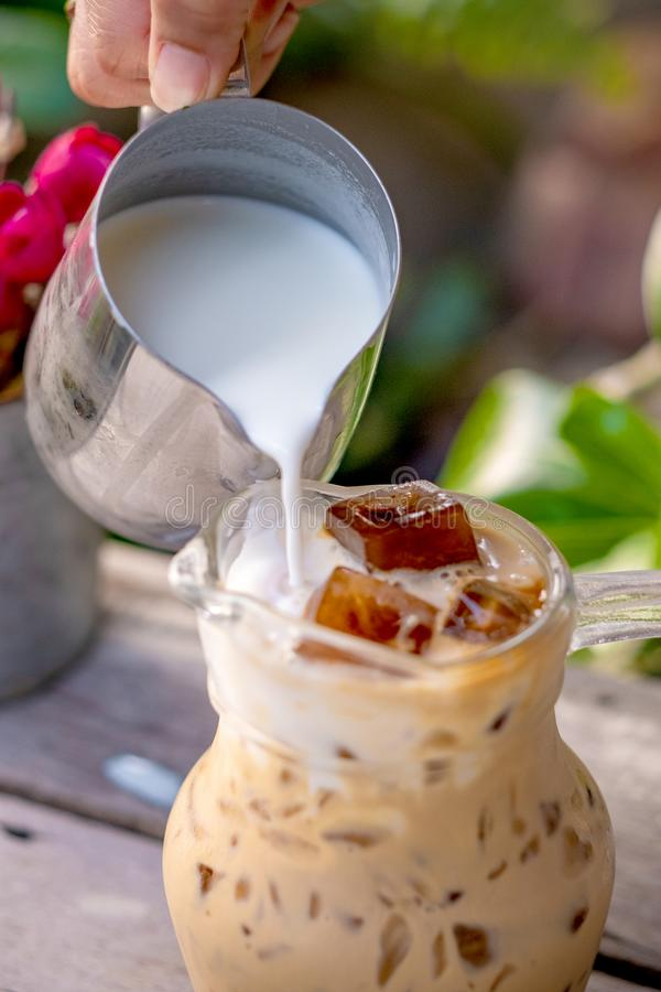 Pouring milk in a glass with latte coffee and iced. On wooden table background stock image