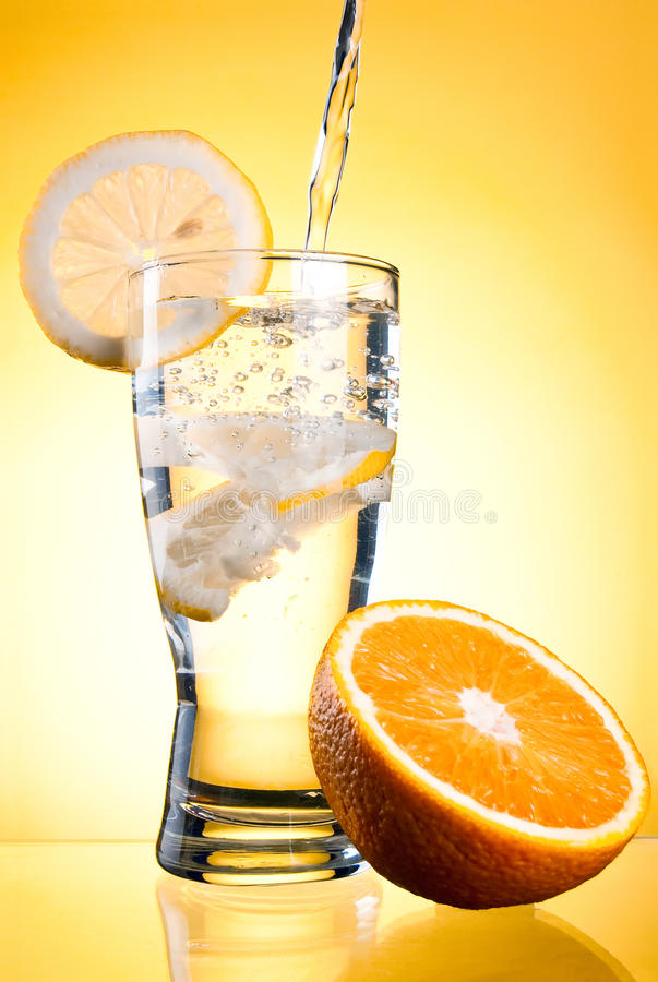 Pouring of mineral water in glass with lemon stock photo