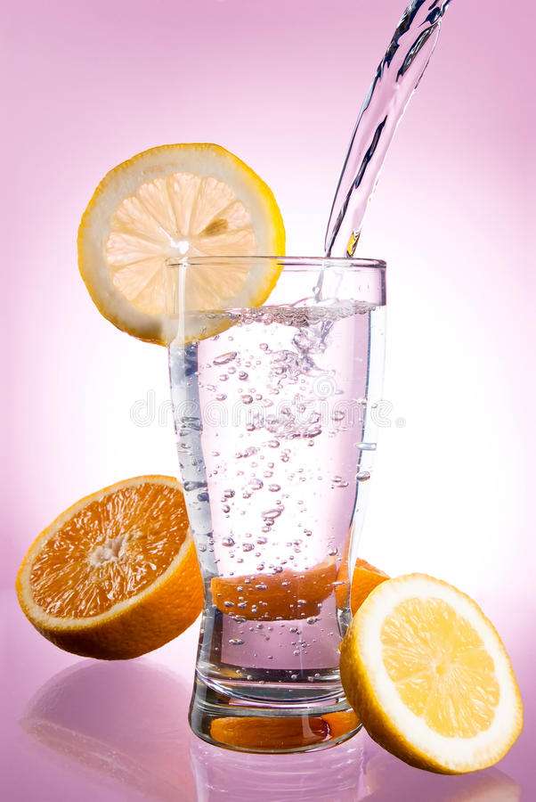 Pouring of mineral water in glass with lemon stock image