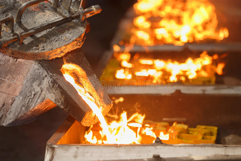 Pouring molten metal to casting mold. Worker pouring molten metal to casting mold stock image