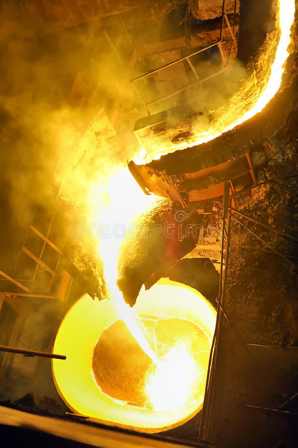 Pouring molten steel in transportation device. In factory royalty free stock photography